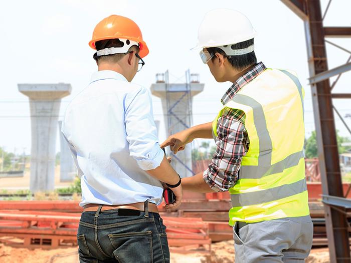 工事現場で話し合っている男性スタッフ