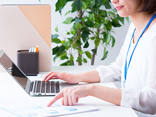 ノートパソコンを操作しながら書類を確認している女性